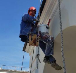 промышленный альпинист красит фасад дома